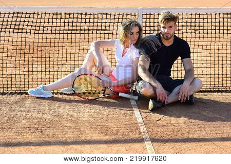 Couple In Love Sit At Tennis Net On Clay Court