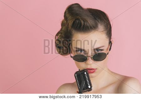 Music look and retro style pinup. Beauty and vintage fashion. Pin up young girl on pink background radio. Woman singer with stylish retro hair and makeup. Girl in glasses sing in microphone.