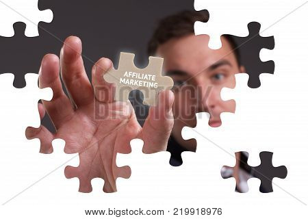 The concept of business technology the Internet and the network. A young businessman collects a puzzle with the proper inscription: Affiliate marketing