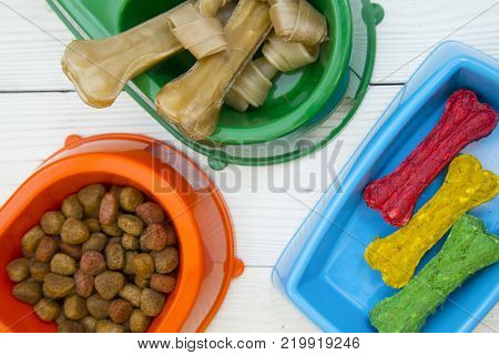 Pet care, veterinary concept. Training and feeding a dog. Blue, orange and green plastic bowls with nutritious dog food and delicious snacks. Close up. White wooden background.