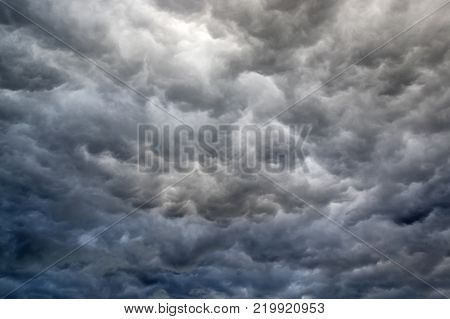 Dark clouds in the sky. Sky covered with whirling, dark rain clouds. The dark color of the clouds sets in a gloomy, depressive mood.