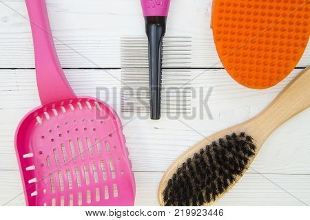 Pet care and grooming concept. Steel, wooden and rubber brushes for animals, a pink pet toilet scoop on a white wooden background, close up.