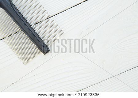 Pet care and grooming concept. A white wooden background with a stainless steel pet brush in the top left. Space for yor text or image.