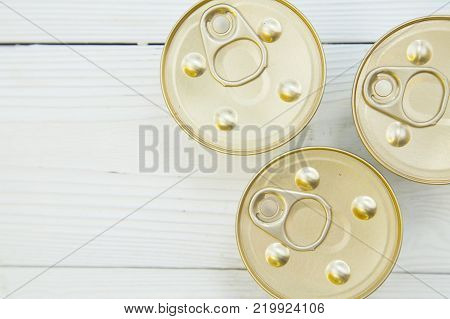 Feeding your pet friend. Three tin cans of pet food , close up. White wooden background. Pet shop banner. Space for your text or image.