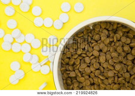 Pet care feeding concept. A nutritious healthy food for a pet. A bowl of dry pet food and vitamin pills on a bright yellow background, close up. Top view. Space for your text or product display.