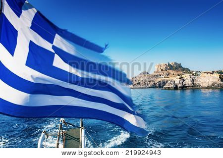 Greek flag and Lindos acropolis in background from boat deck (Rhodes Greece)