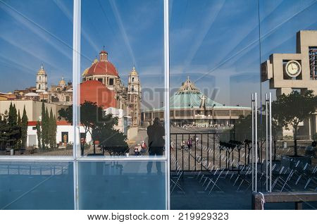 VILLA OF GUADALUPE, MEXICO CITY, DECEMBER 04, 2017 - Atrium of the Americas with the Carrillon and the two basilicas in the background reflected in the glass of the public dining room for pilgrims.