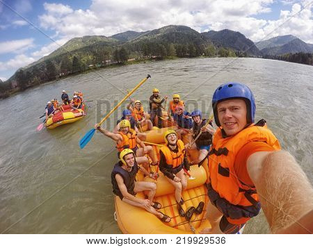 mountain Altai RUSSIA - July 16 2017: man in helmet holds action camera and makes selfie on background of friends with oars rafting