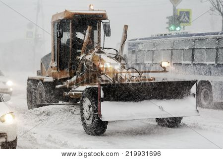 Snow plow truck removes snow from road during heavy snow winter storm and poor (low) visibility. Winter highway maintenance in Petropavlovsk-Kamchatsky City