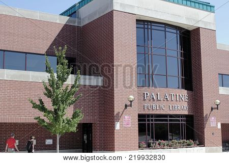 Palatine, IL, USA - August 8, 2017: Two people walking to the Palatine Public Library entrance. Palatine Public Library being visited by two people in the day.