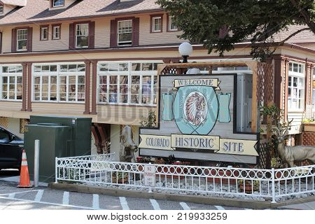 Idaho Springs, CO, USA - August 27, 2017: Welcome, Indian Hot Springs, Colorado Historic Site sign at main entrance in the day. Signs and building of Indian Hot Springs.