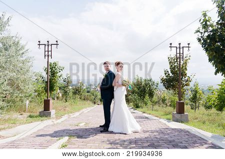 Portrait of a lovely couple honeymooned on a wedding day with a bouquet in hands looking at each other laughing and smiling against a green alley outdoors. Concept of a happy young married couple