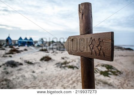 Wooden tourist pointer, travelers with backpacks on a plate