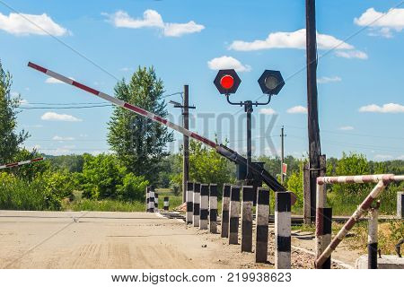 A  closing barrier and red traffic light at the railway crossing. railway station.