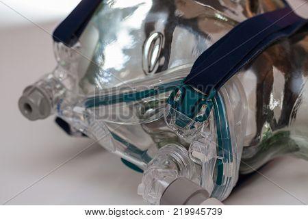 Closup of Full face sleep apnea mask on clear glass head.