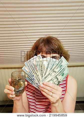 vertical image of a woman's face hiding behind a hand full of American money