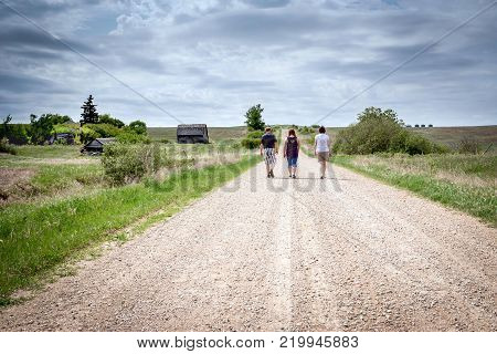three grown adults walking down a  rural gravel road with a barn standing in the distance under a cloudy sky on a warm summer day.