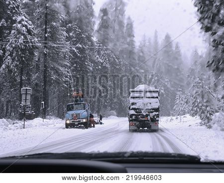 View from the car window on winter road with trucks and car. Heavy snow.