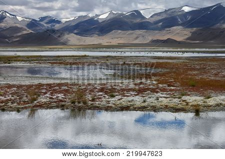 Thunderstorm on the high mountain lake: gloomy heavy clouds descend to the tops of the hills and are reflected in the water surface, Ladakh, Himalayas, Northern India.