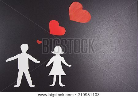 Love of man and woman. Paper silhouettes of lovers with red hearts over them on black background. concept for day of all lovers. Valentine's Day