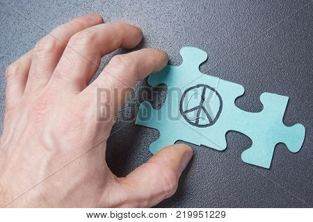 hand of person collects puzzle with symbol of pacifism. Peace sign on puzzle. World Day of Peace concept
