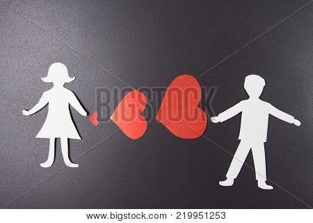 concept of love. Red hearts between man and woman of paper on black background. The idea for Valentine's Day and day of all lovers