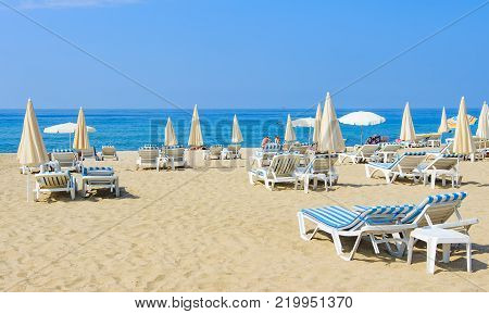 Luxury resort beach with umbrellas and sun beds on white sand near blue sea on bright sunny day. Tropical beach with tourists. Summer vacation concept
