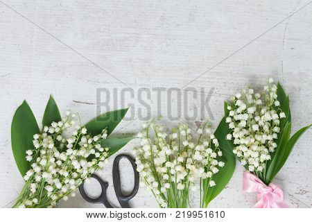 Lilly of the valley flowers with leaves border on white wooden background