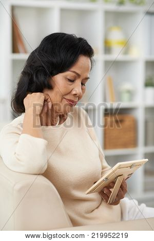 Smiling wistful senior woman looking at photo in frame