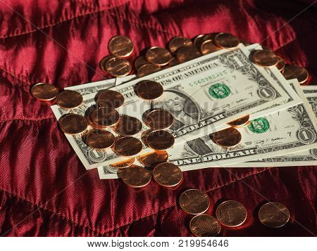 One Dollar banknotes and One Cent coin money (USD), currency of United States over crimson red velvet background