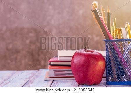 Back to school, Close up red apple,pencil and notebook or notepad with morning sunlight on wooden table with blurred background and copy space for design.