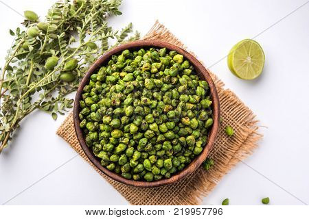 Roasted fresh Green Chickpeas or Chick Peas or harbara in hindi also known as Cicer with pinch of salt and chat masala and lemon