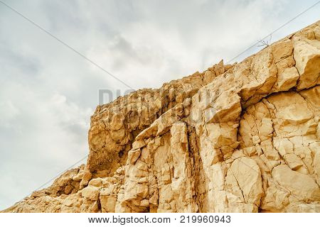 View on rock in dry desert in Israel. Valley of sand, rocks and stones in hot middle east tourism place. Scenic outdoor view on wild mountain. Summer heat and sunlight, nobody on photo