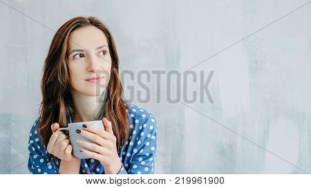 Cute happy woman relaxing in the bed dressed in blue pyjamas with white dots drinking hot tea. Sleepy morning at home. Lazy weekend concept.