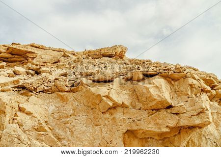View on rock in wild desert in Israel. Valley of sand, rock and stone in hot middle east tourism place. Scenic outdoor view on wild land. Summer heat and sunlight with nobody on photo