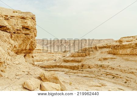 Outdoor summer landscape view on dry desert in Israel. Valley of sand, rocks and stones in hot middle east tourism place. Scenic outdoor view on wild land. Summer heat and sunlight, nobody on photo