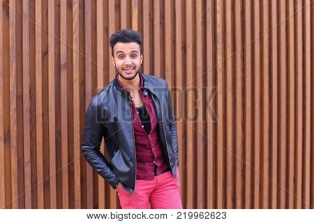 Charismatic Young Businessman Muslim Man Comes Closer to Camera, Smiles and Poses For Camera on Photographer, Shows Gestures, Laughs, Advertises Clothing on Wooden Panel Background Stairs Outdoors. Stylish Young Man With Dark Hair