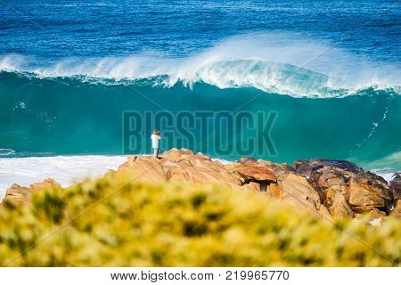 Young man standing on rocks watching large crashing waves in Yallingup between the towns of Margaret River and Dunsborough in the south west of Western Australia.