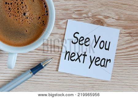 See you next year - memo at wooden office table. 2018 new year coming.