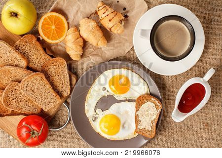 Top view of plate with fried eggs and toast with butter, cup of coffee, croissants, orange, apple, bread on wooden cutting board, fresh tomato and ketchup in a sauce boat on table covered with sackcloth