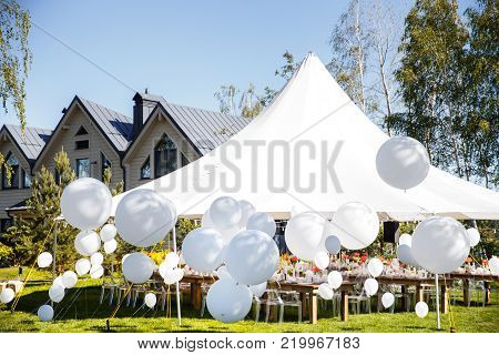 Wedding tent with large balls. Tables sets for wedding or another catered event dinner.