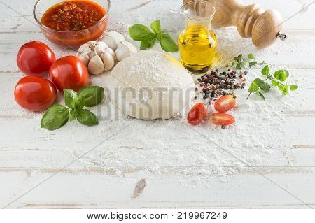Food ingredients and spices for cooking, tomatoes, oil, pepper, salt, garlic, basil, oregano and delicious italian pizza dough with napkin, fork and spoon on white wood background. Top view.