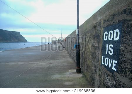 God is Love sign on Gardenstown Harbour, Scotland