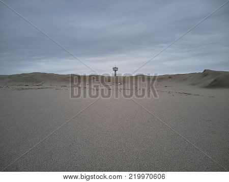 Beach with sand dunes and the aqueduct tower in the background.