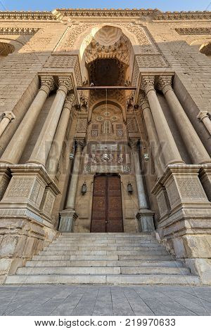 Entrance of al Rifai Mosque with closed decorated wooden door, ornate columns, ornate recessed stone wall and stairs, Old Cairo, Egypt