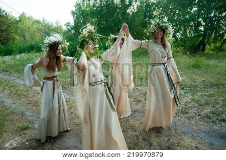 Attractive Women with Wreath of Flowers walking in forest. Ivan Kupala Holiday Celebration