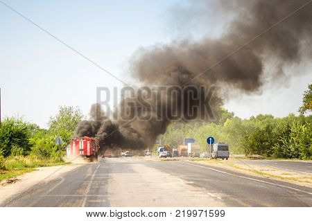 Burning motor vehicle after road accident and arrival of fire truck with rescue rangers at highway.