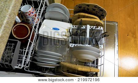 Overhead view Open dishwasher full with used dirty utensils in it.