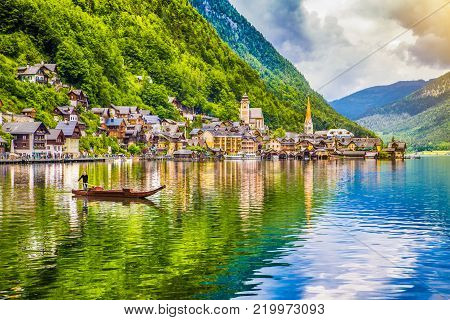Scenic picture-postcard view of famous Hallstatt mountain village with Hallstätter See and traditional Plätte boat in the Austrian Alps, region of Salzkammergut, Austria