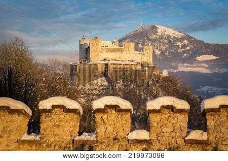 Classic view of famous Festung Hohensalzburg in the historic city of Salzburg illuminated in beautiful golden evening light with blue sky during Christmas time in winter, Salzburger Land, Austria